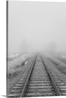 Railroad tracks fade into the morning fog