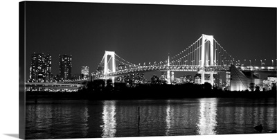 Rainbow bridge with reflection at night.