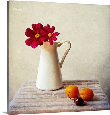 Red flowers in white vase and fruits on table.