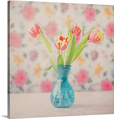 Red-yellow tulips in blue glass vase with floral-printed wallpaper behind.