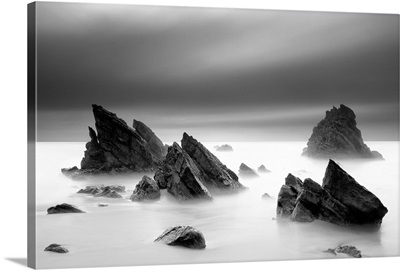 Rocks in sea against cloudy sky in Sintra, Adraga.