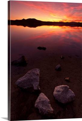 Rocks on beach at sunset.