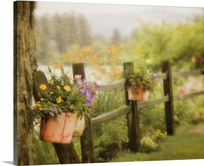 Rustic wooden fence with flowers in clay pots hanging on posts