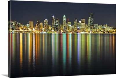 Seattle skyline at night with reflection in water of sea.