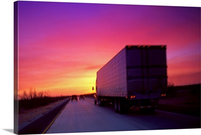 Semi-truck on road at sunset
