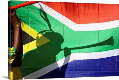 Shadow of soccer supporter blowing vuvuzela, South African flag in background