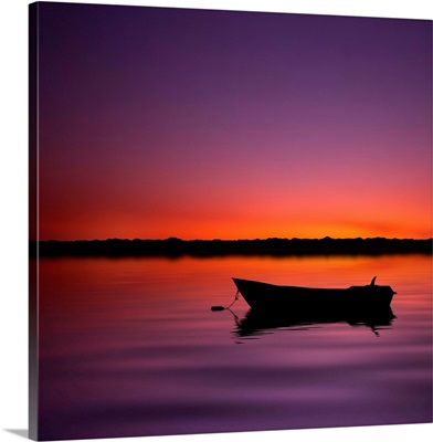 Silhouette boat in lake with sunset.