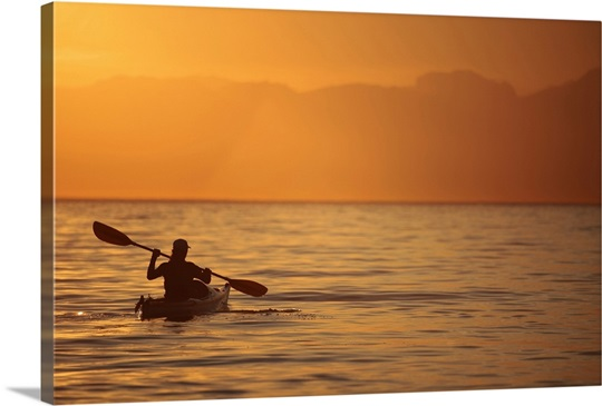 Silhouette Of A Woman In Sea Kayak At Sunset