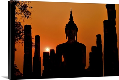 Silhouette Of Ancient Buddha Statue Sitting In Middle Of Ruined Temple