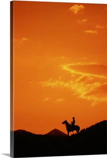 Silhouette of cowboy riding horse at sunset