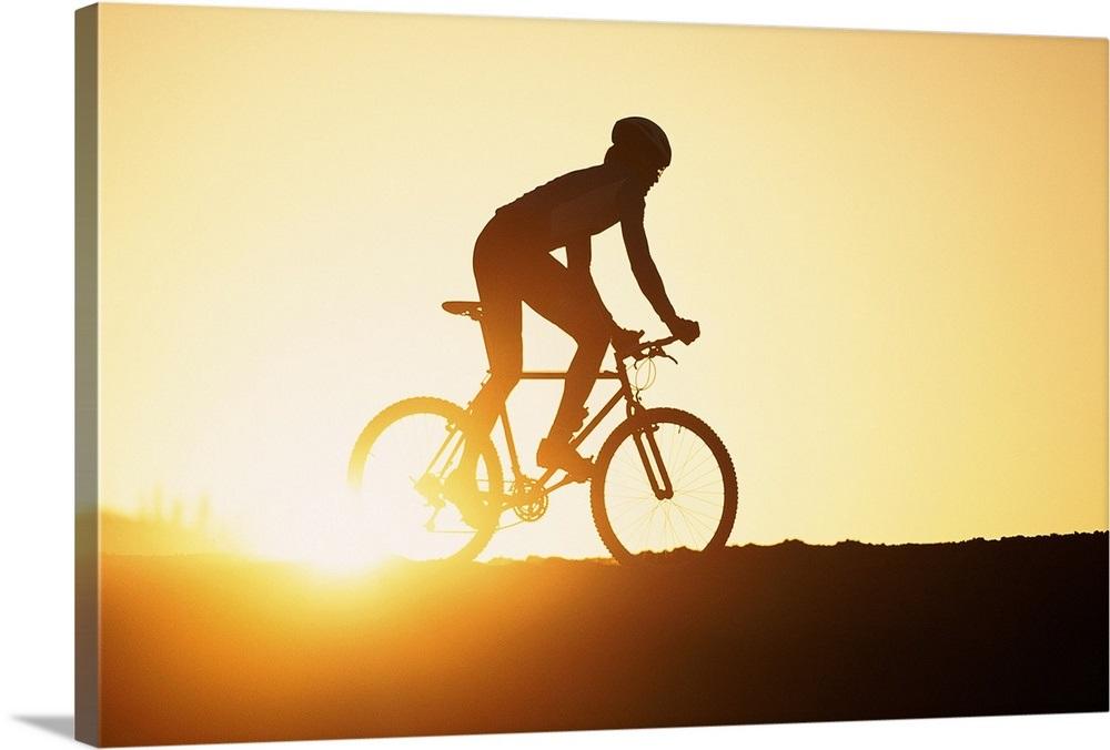 Silhouette of man riding mountain bike at sunset