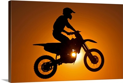 Silhouette of motocross race in mid air at sunset.