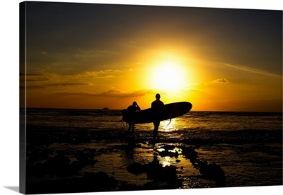 Silhouette surfers on beach at sunset.