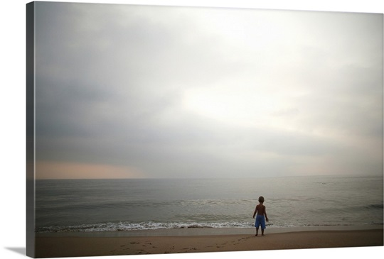 Small boy looking at sky and ocean