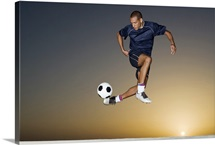 Soccer player kicking ball in mid air