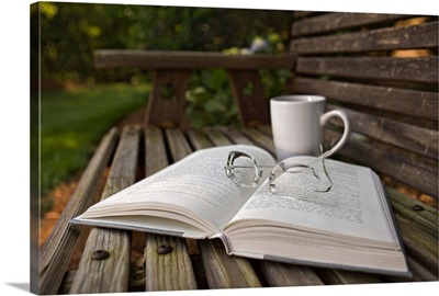 Still life of open Book, eyeglasses and coffee cup on wooden bench