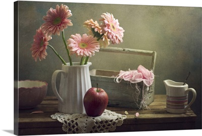 Still life with pink gerberas and red apple on table.