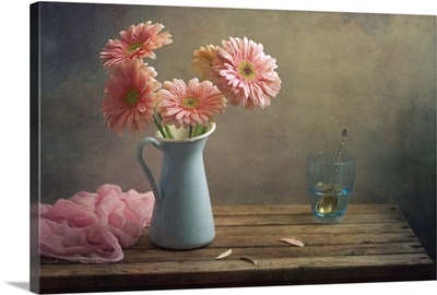 Still life with pink gerberas flowers in blue pitcher jug anf glass of water.