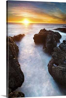 Sunset at seashore with rocks and surf, US.
