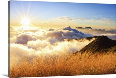 Sunset over mountains with sea of clouds below.