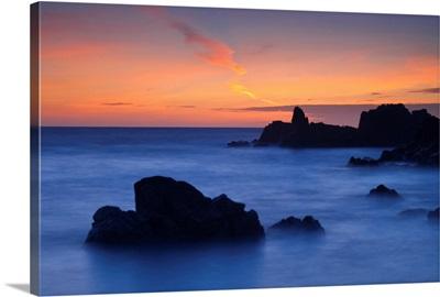 Sunset over rocky California coastline of Pacific Ocean