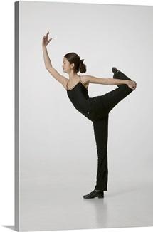 Teenage girl (14 15) performing gymnastic in studio, portrait