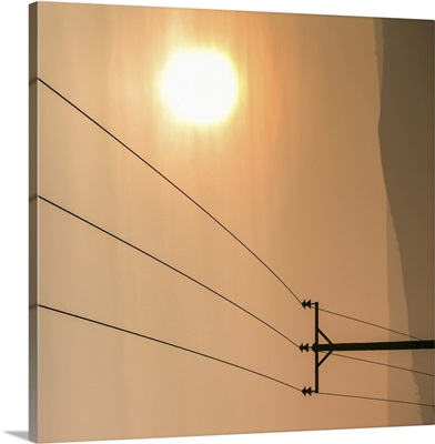 Telephone wires and pole with sunset in background.