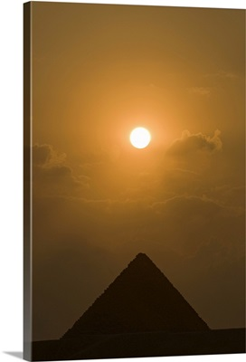 The sun begins to set above The Great Pyramid of Giza, in Cairo, Egypt.