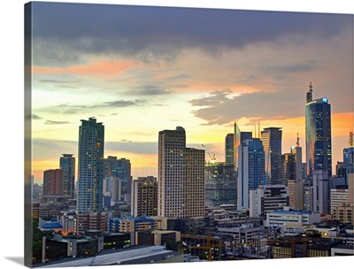 The sun setting light up low clouds over the Makati City, Manila Skyline.