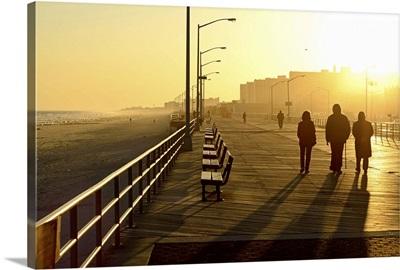 Three people walking down boardwalk near beach at sunset.