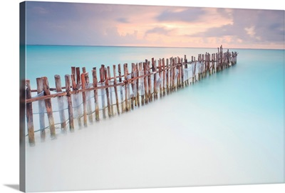 Tranquil scene of Wooden posts in Caribbean sea, at sunset right after storm.