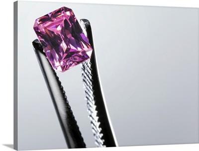 Tweezers holding small purple gem, close-up