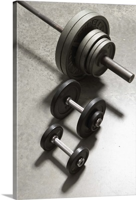 Two dumbbells and barbell side by side on concrete floor