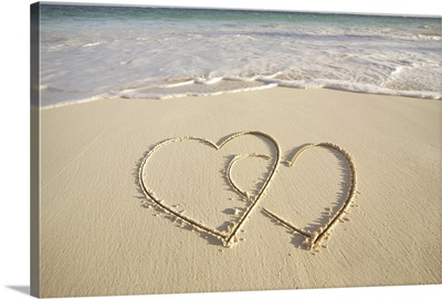 Two overlying hearts drawn on the beach with incoming surf.