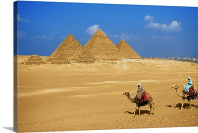 Two people riding camels near the pyramids of Giza, Egypt