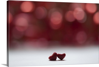 Two red hearts and red bokeh background