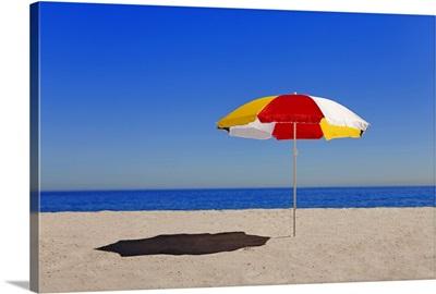 Umbrella in sand on empty beach