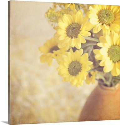 Vase full of yellow flowers in soft hazy natural light.