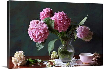 Vase with Hortensia flowers on brown table with bowl, saucer, flowers.