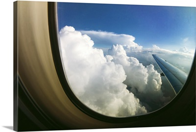 Watching the clouds pass by through a window of an airplane