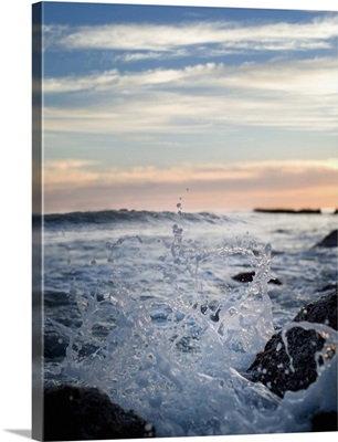 Wave splashing against rocks on shore in the evening, sun is setting in background