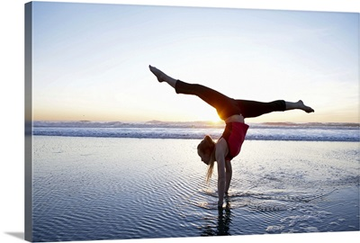 Woman doing a hand-stand on the beach at sunset