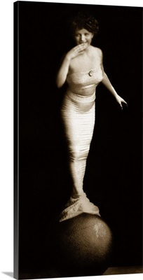 Woman in mermaid costume balancing on ball