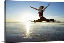 Woman leaping over the ocean