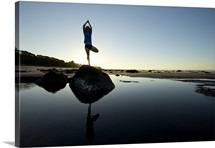 Woman practicing yoga on rocks by sea.