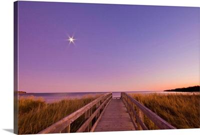 Wooden boardwalk leading through golden grasses to beach at sunset