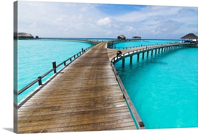Wooden jetty to seaplane landing over crystal clear water with cloud dusted blue sky.