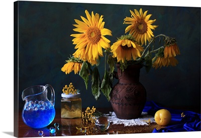 Yellow flowers in vase, plums, gel balls on table.