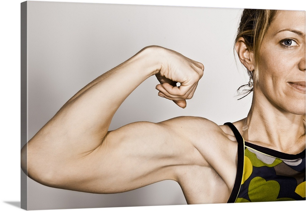 Young Blond Female Flexes Bicep Muscle While Smiling Wall Art