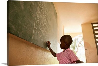 Young boy in school writing on chalkboard